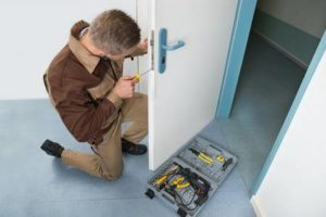 42544867-high-angle-view-of-male-carpenter-with-screwdriver-fixing-door-lock